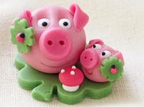 Marzipan pig with cloverleaf and mushroom on white